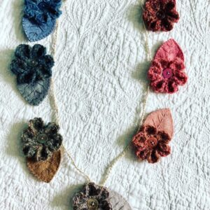 Handmade using 100% Alpaca wool and felt garland. A handmade, crocheted and sewn flower and leaf garland in a range of tonal hues. Burgundy through to Navy Blue. Seven Flower and leaf decorations along the garland.