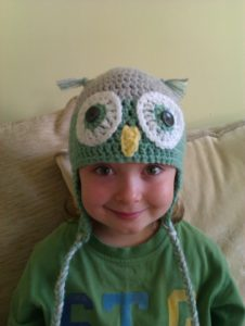 Cosy grey and pale green crocheted owl hat.