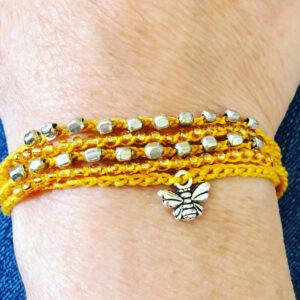 5 strand, fully adjustable bracelet with glass beads and silver metal coloured bee charm. Handmade using 100% cotton. Eco-friendly and fully recyclable.