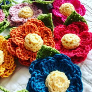 A hand crocheted garland of double layered flowers with crocheted centre and leaf details. Made in a rainbow of colours using 100% cotton.
