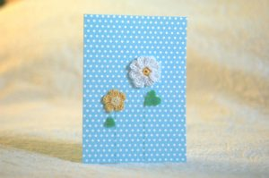 Hand made and hand stitched, white and yellow crocheted flowers and green felt leaves greetings card. Left blank inside for your own message. Size w12.7 x h17.7cm