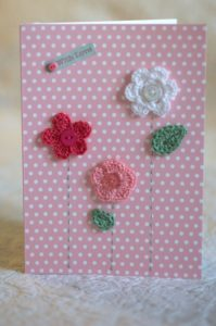 Hand made and hand stitched, pink and white crocheted flowers and green crocheted leaves greetings card and 'with love' tag on front. Left blank inside for your own message. Size w12.7 x h17.7cm