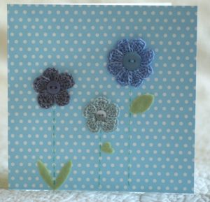 Hand made and hand stitched, blue and grey crocheted flowers and green felt leaves greetings card. Left blank inside for your own message. Size w15.2 x h15.2cm