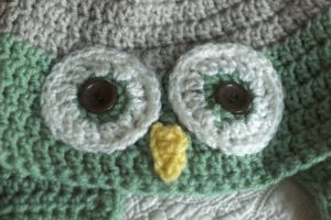 Grey and pale green cosy crocheted owl hat.