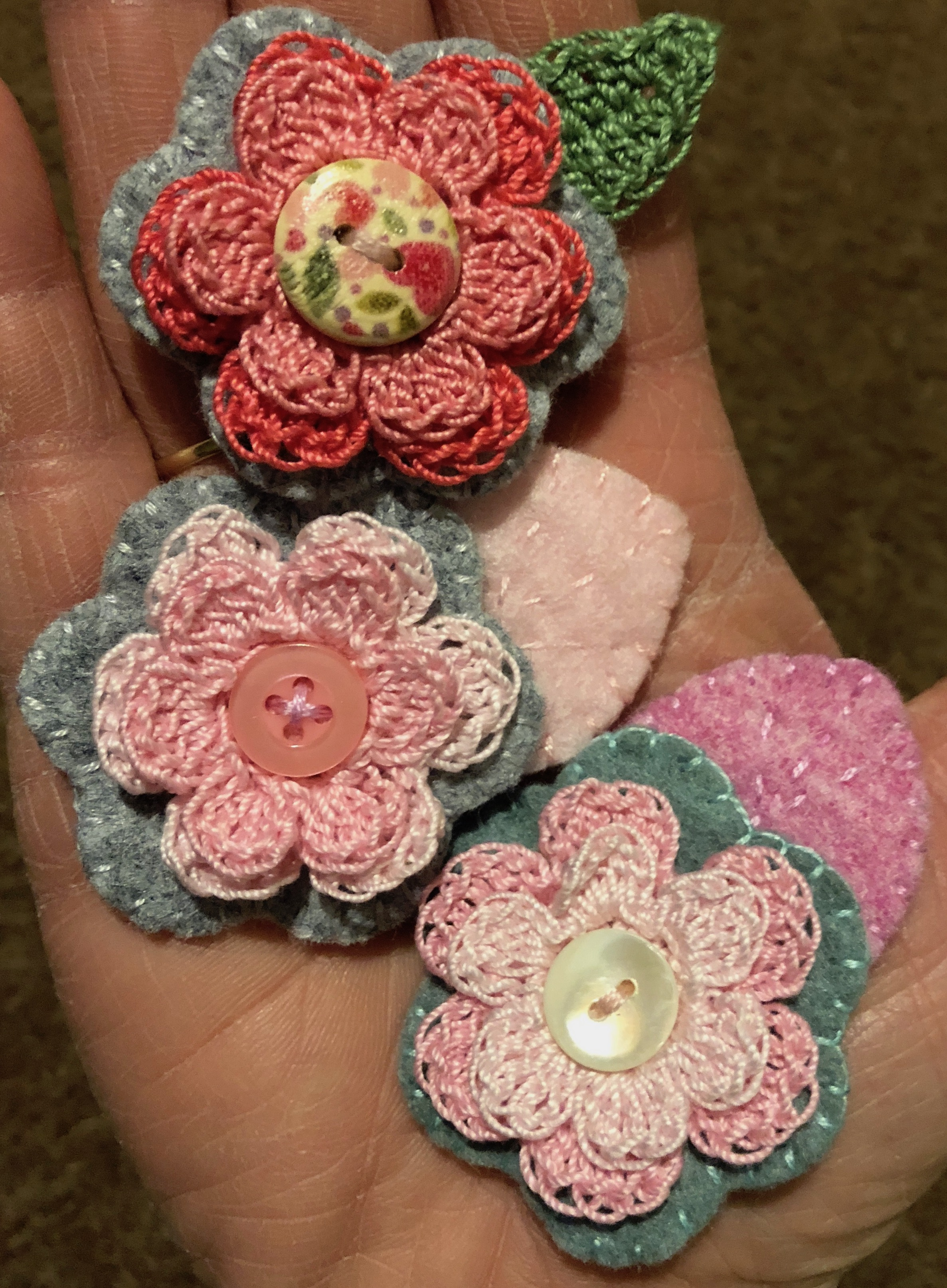A hand-full of little flower brooches.
