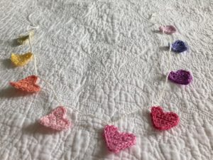 Tiny crocheted hearts bunting in a rainbow of colours.