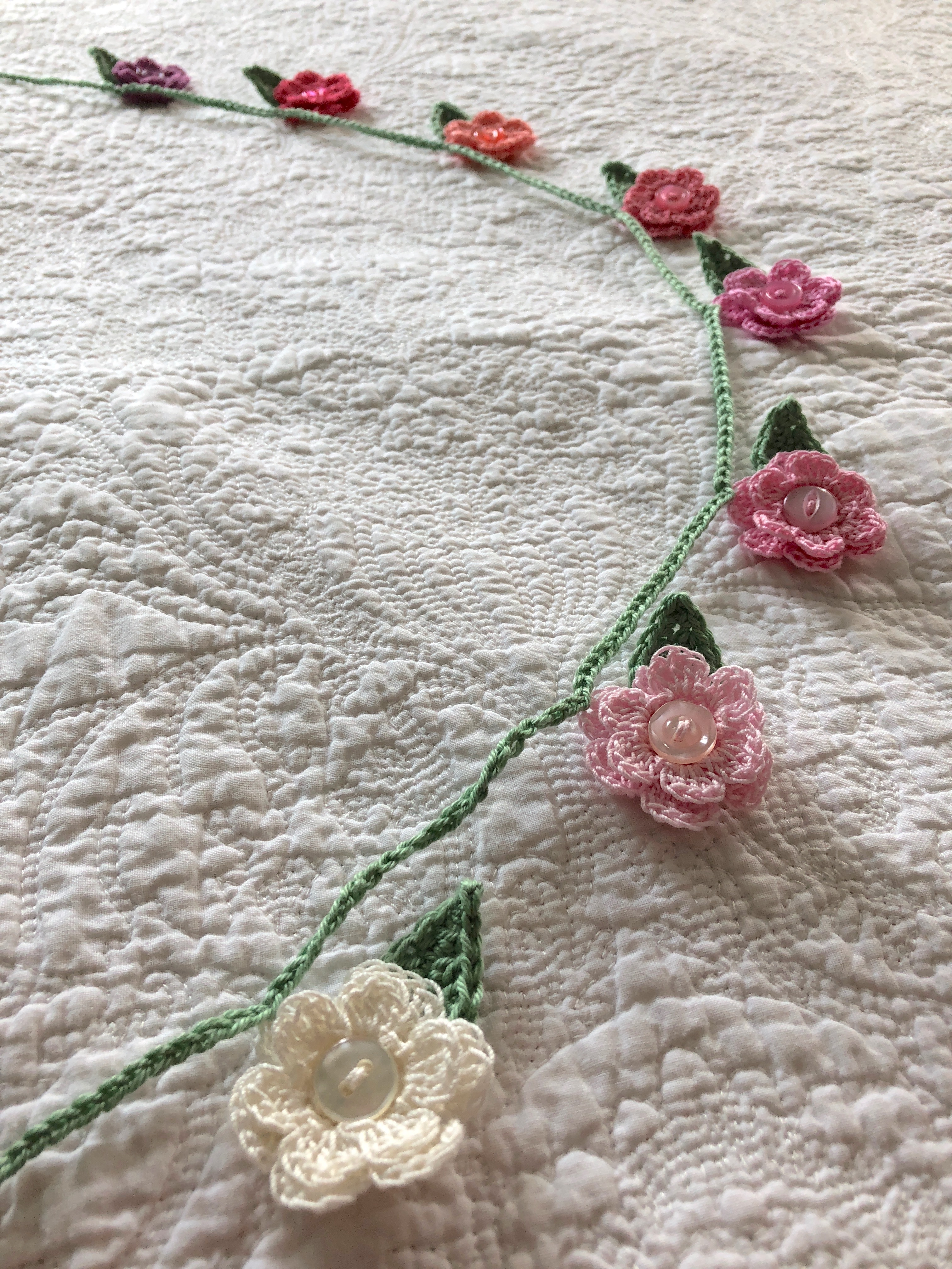 A hand crocheted small flower and leaf garland in graduated colour way from white through pinks to purple.