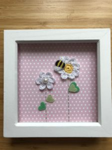 Hand crocheted white daisy flowers and hand embroidered bumblebee picture on pink polkadot background in a white wooden frame.