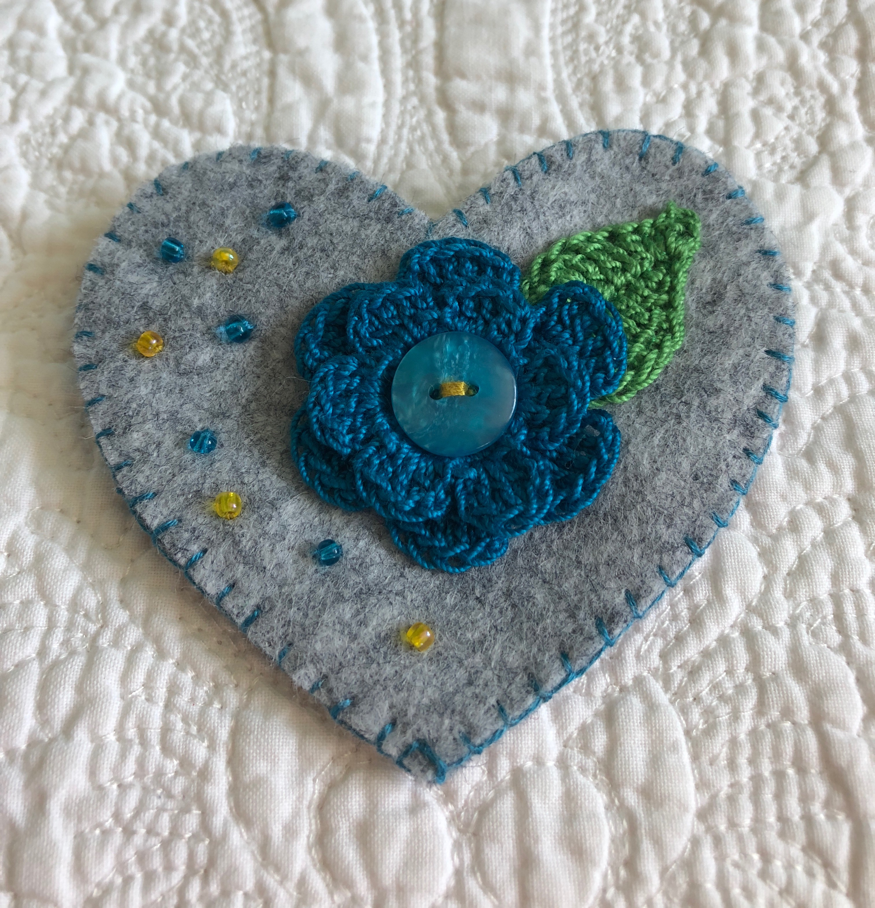 Handmade and hand stitched grey felt heart with a blue crocheted flower and green leaf embellished with a button and tiny glass beads.