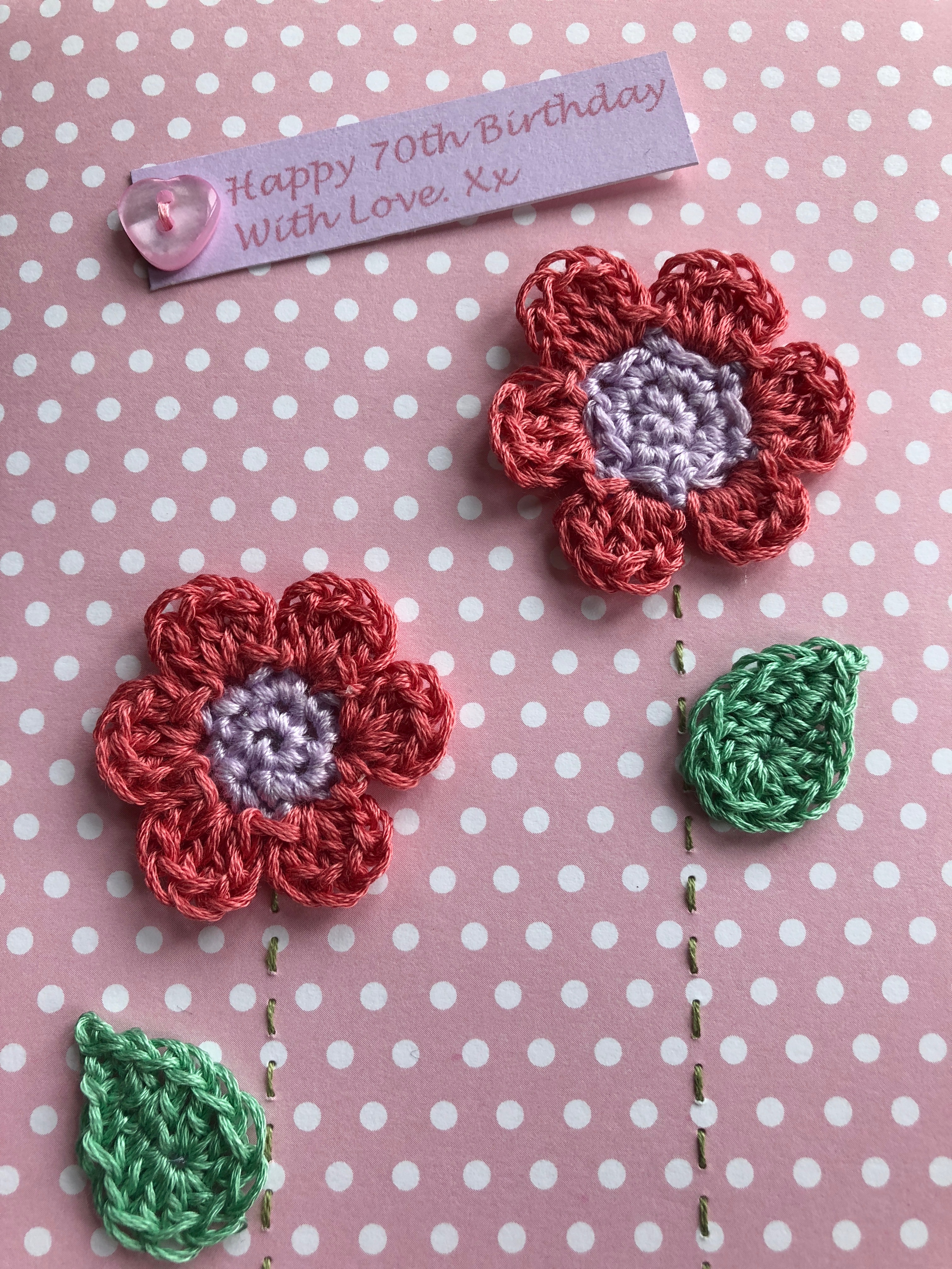 A handmade, crocheted and stitched card with two pink and lilac crocheted flowers with green crocheted leaves and a printed message with hand sewn button detail.