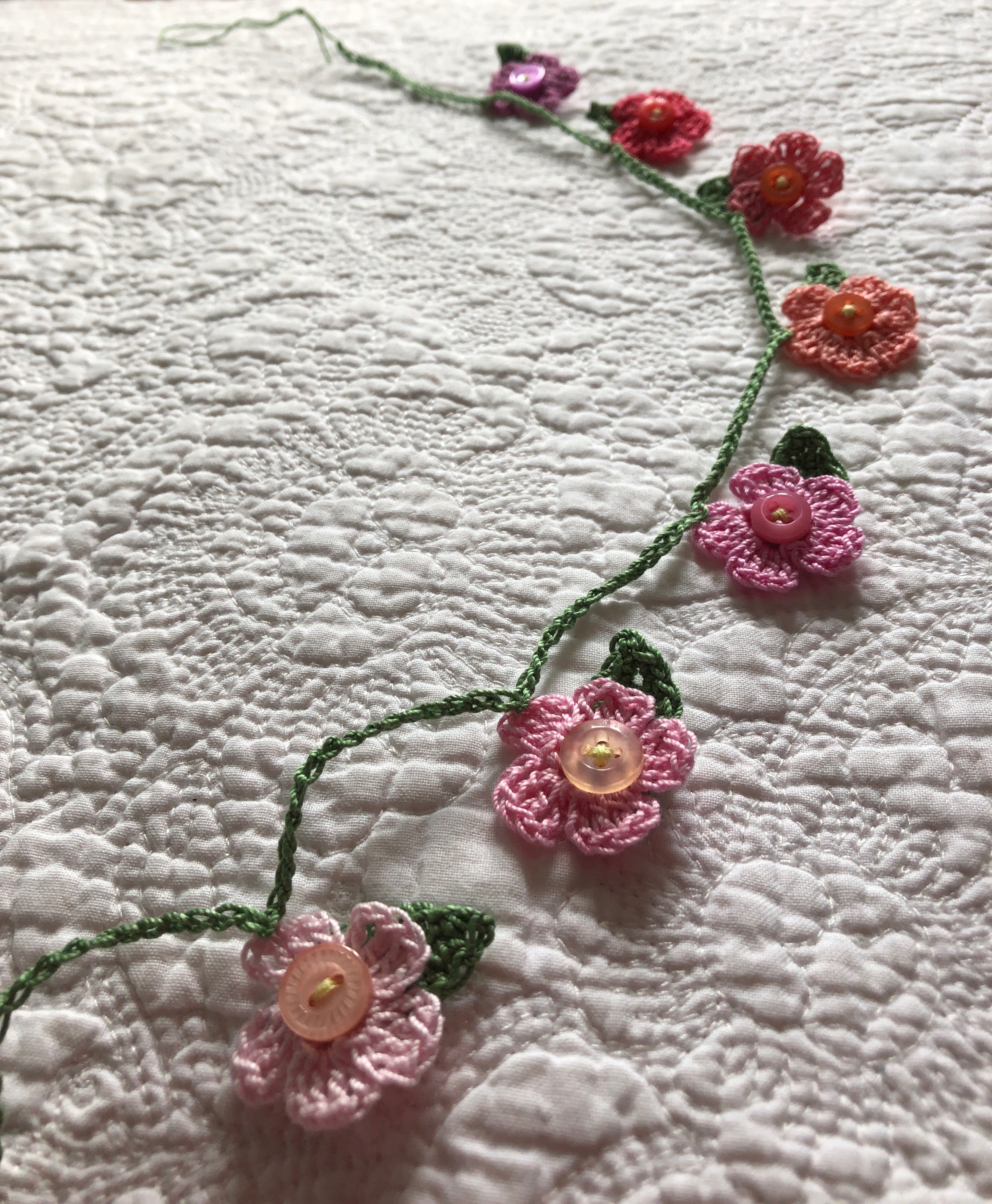 A handmade, crocheted garland of tiny flowers and leaves with a button detailing. The flowers are in a gradient of pastel shades from pale pink to purple.