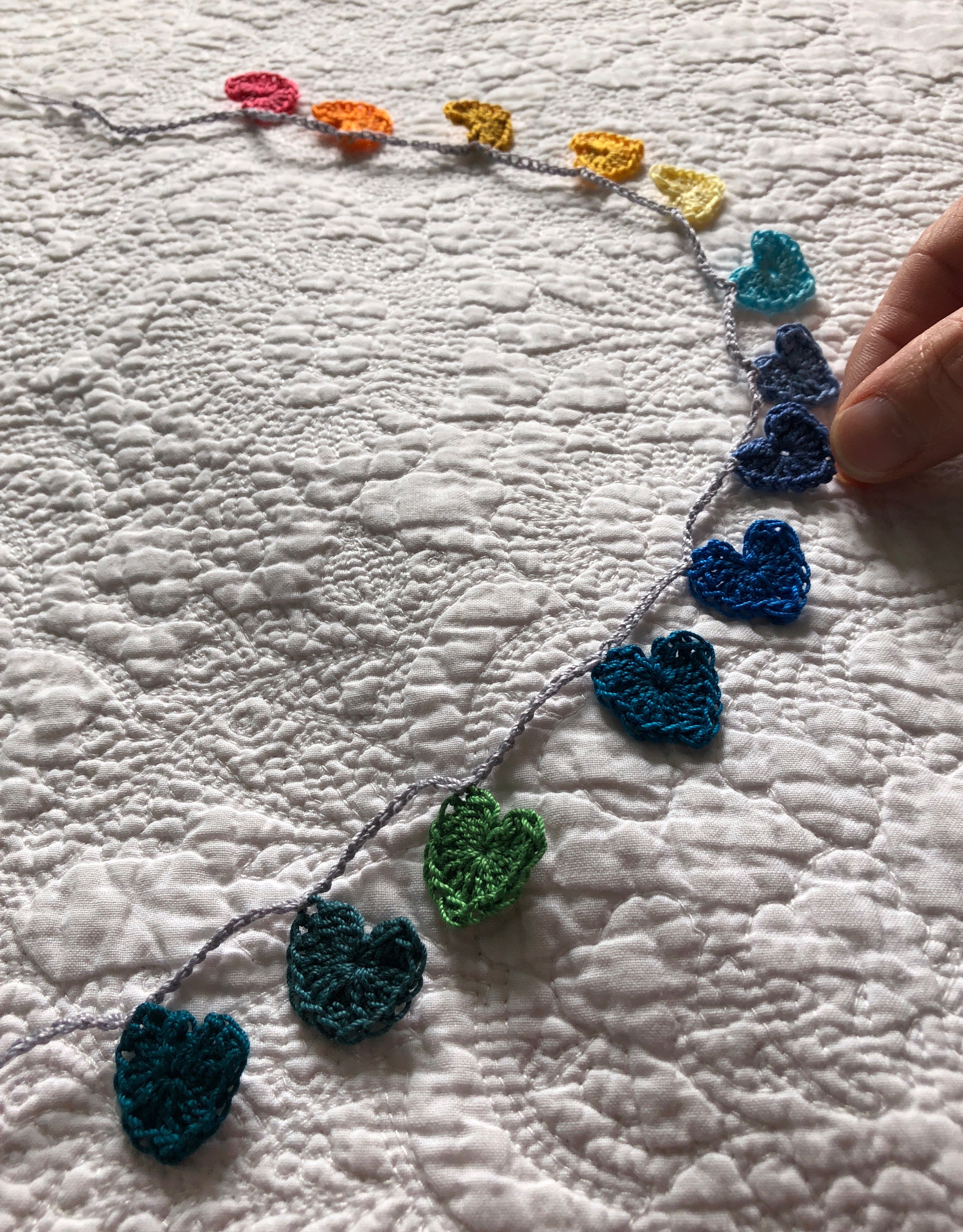 Tiny cotton crocheted hearts garland in a rainbow of colours grading from petrol blue through to pink.