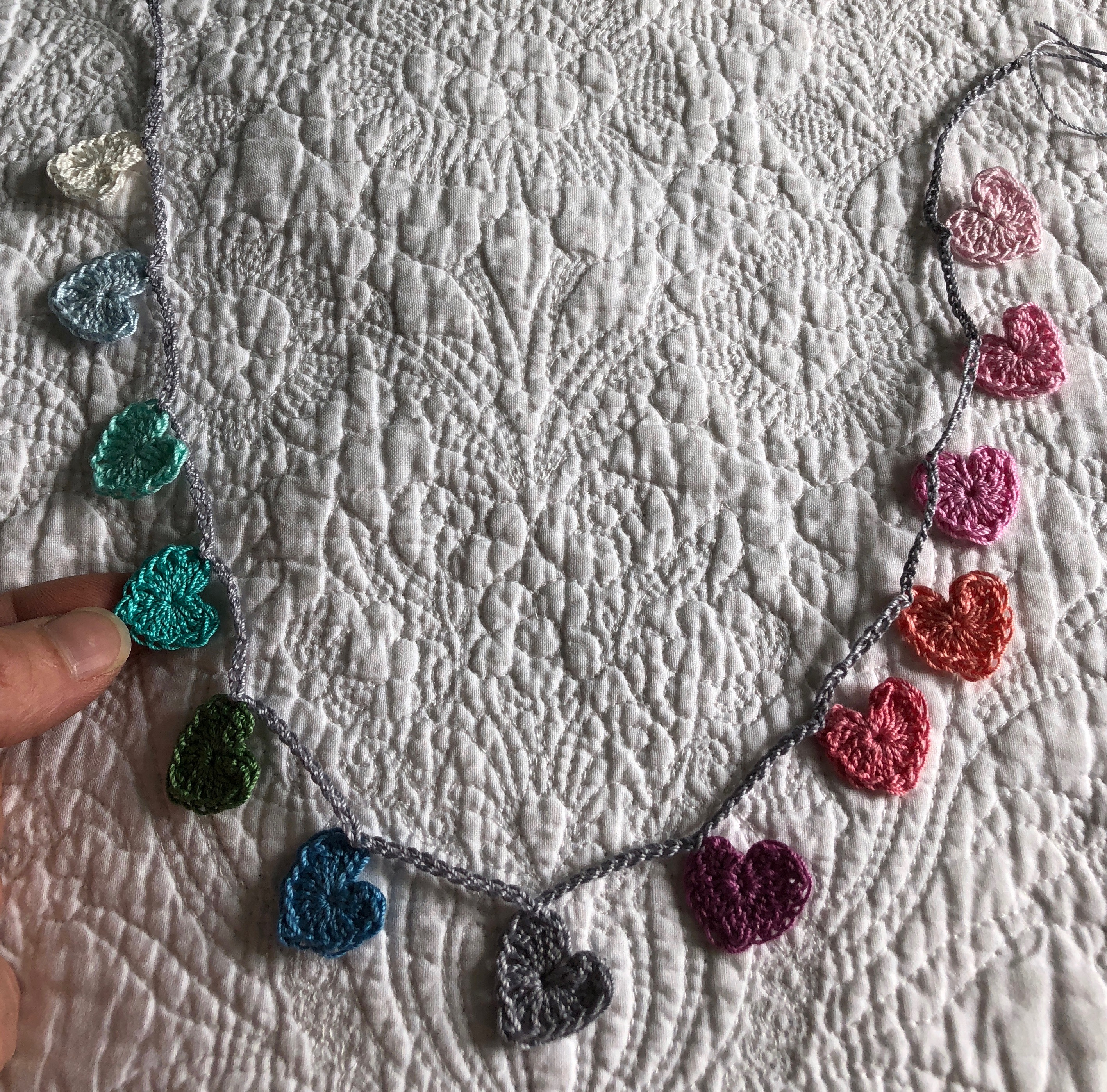 Tiny cotton crocheted hearts garland in a rainbow of pastel colours grading from white, pale blue through to pink.