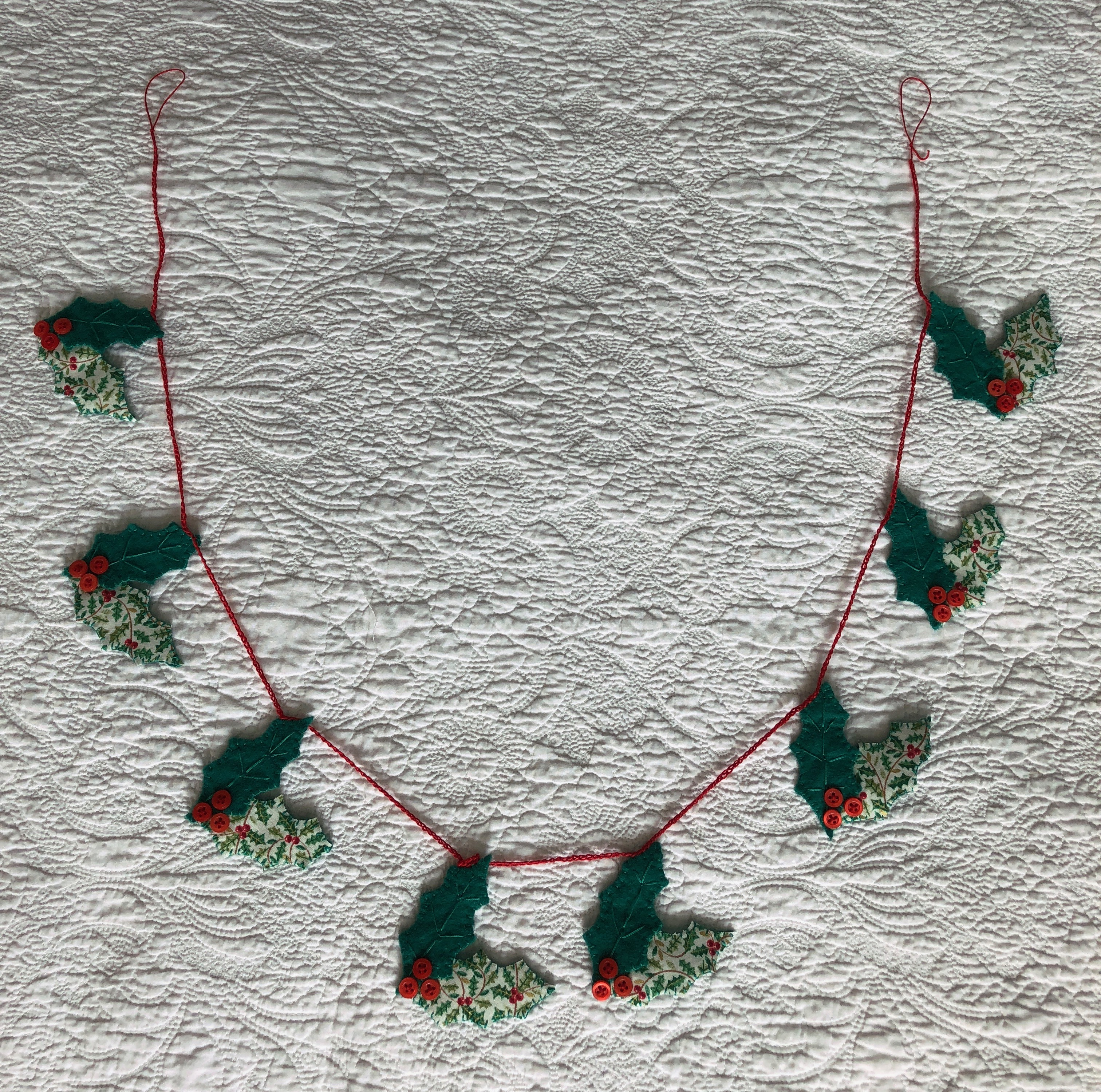 A handmade, hand stitched garland of green felt and holly printed cotton fabric holly leaves with red button berries.