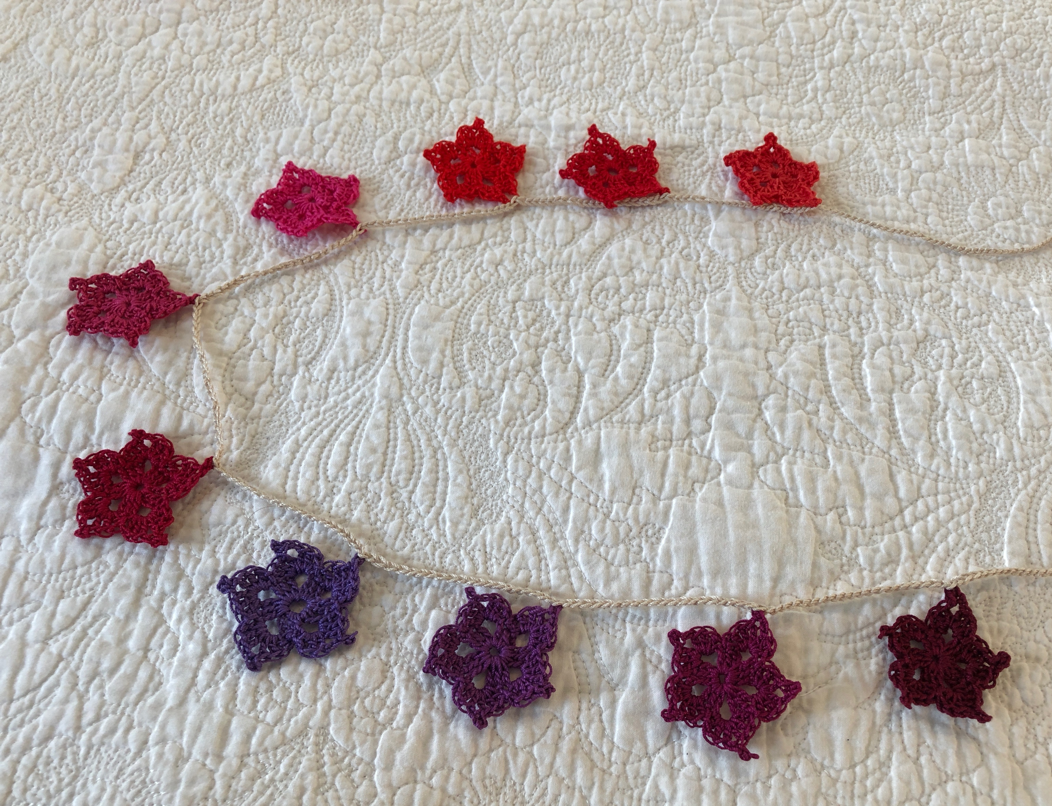 Hand made, crocheted, vintage style, cotton star garland in a gradient of red to purple shades.