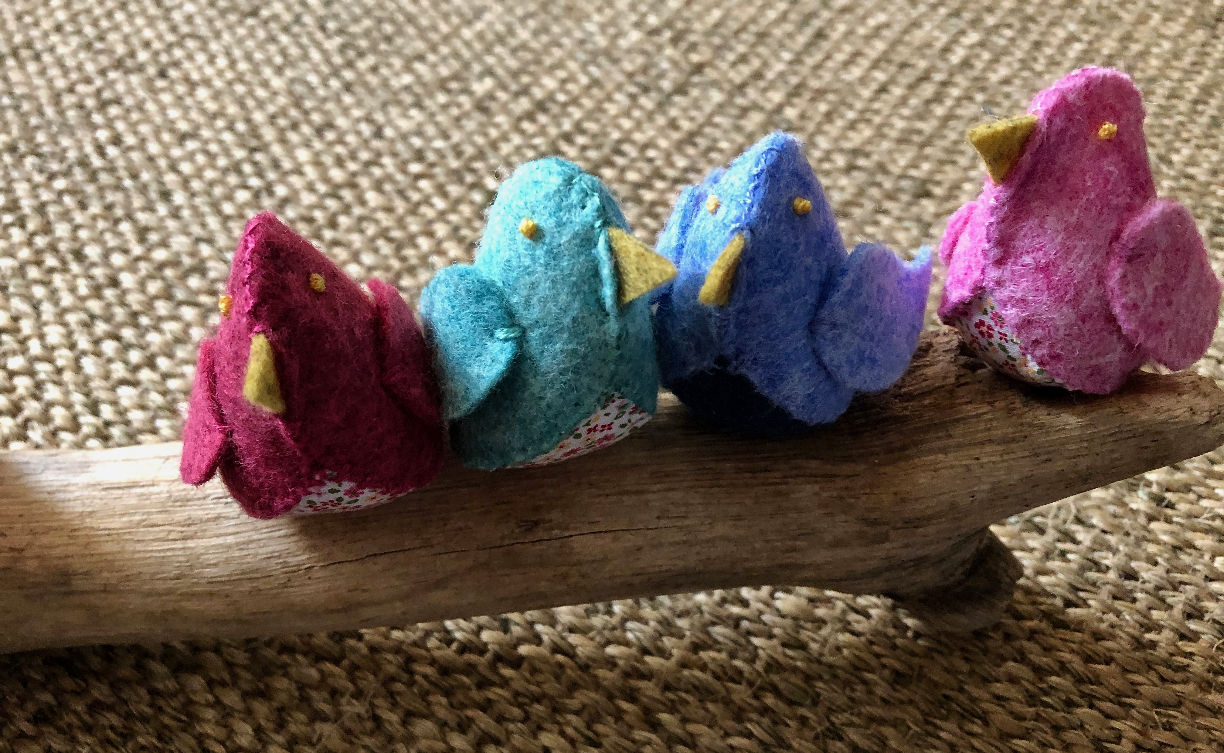 A family of 6 handmade and hand stitched felt and fabric birds sat on a drift wood log. Birds are made in a range of complimentary pastel shades of blue, green and pink with tiny flower fabric chests or wings.