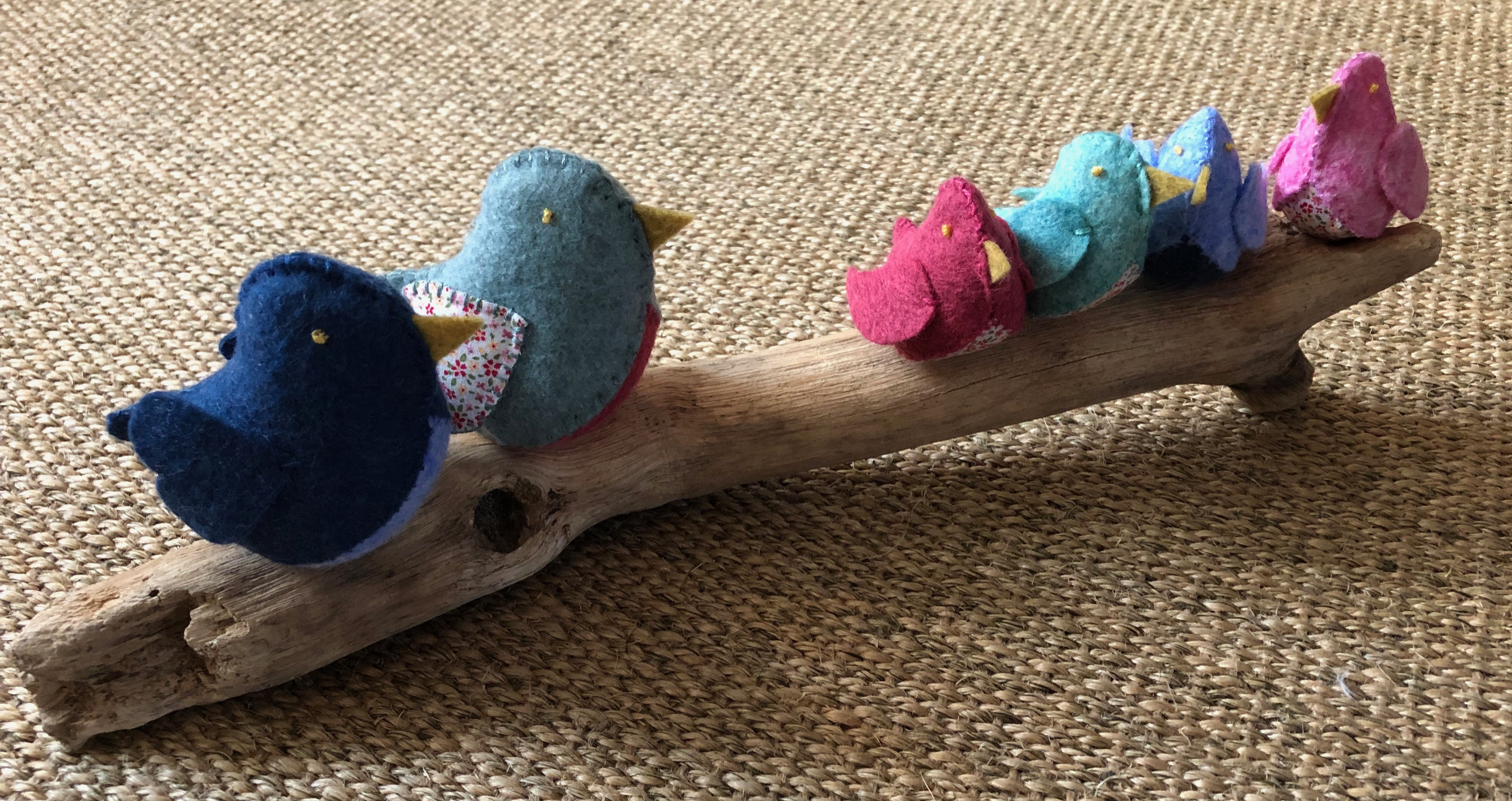 A family of 6 handmade and hand stitched felt and fabric birds sat on a drift wood log. Birds are made in a range of complimentary pastel shades of blue green and pink with tiny flower fabric chests or wings.