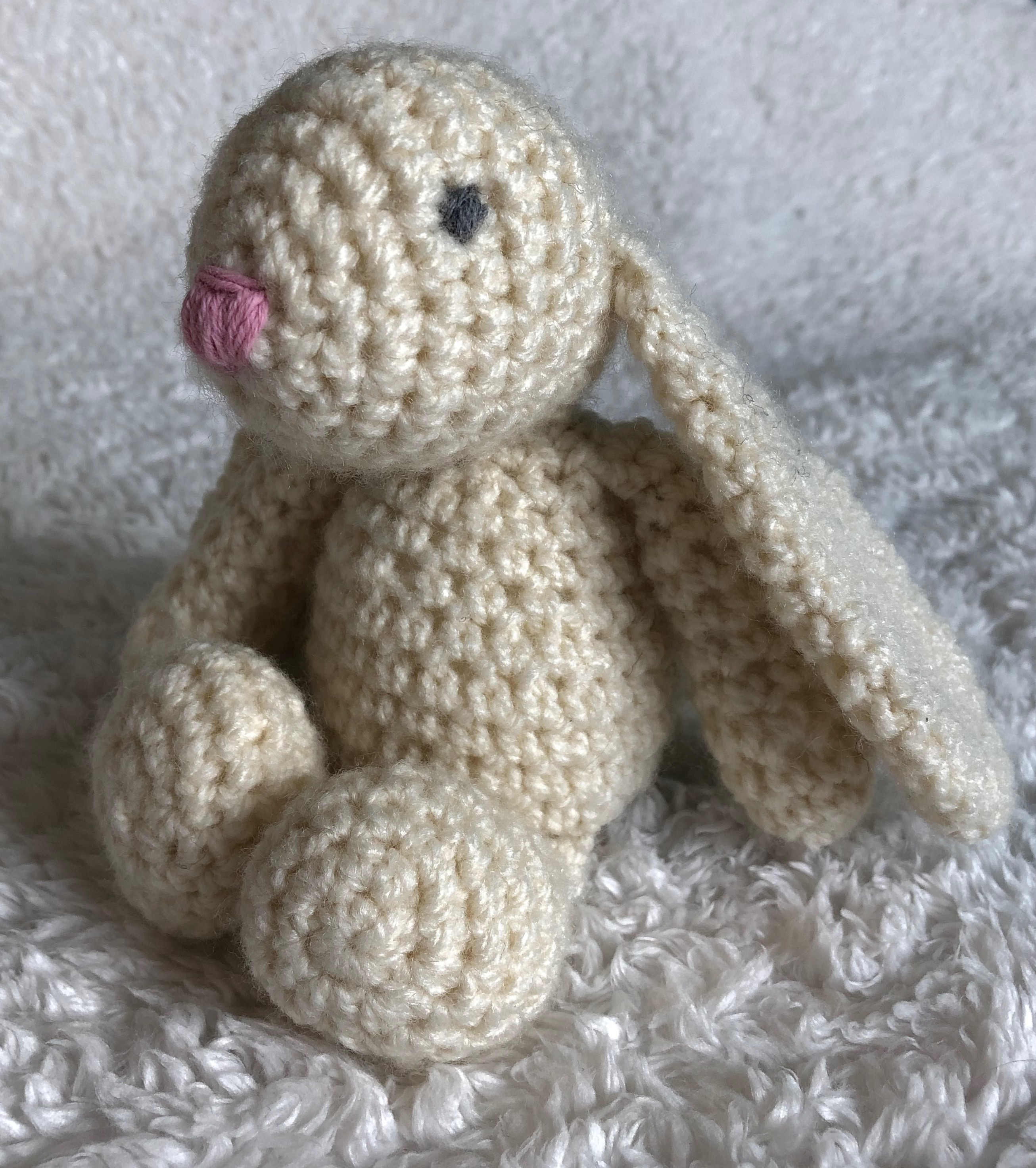 A small handmade, crocheted cream bunny rabbit with a pink crocheted heart.