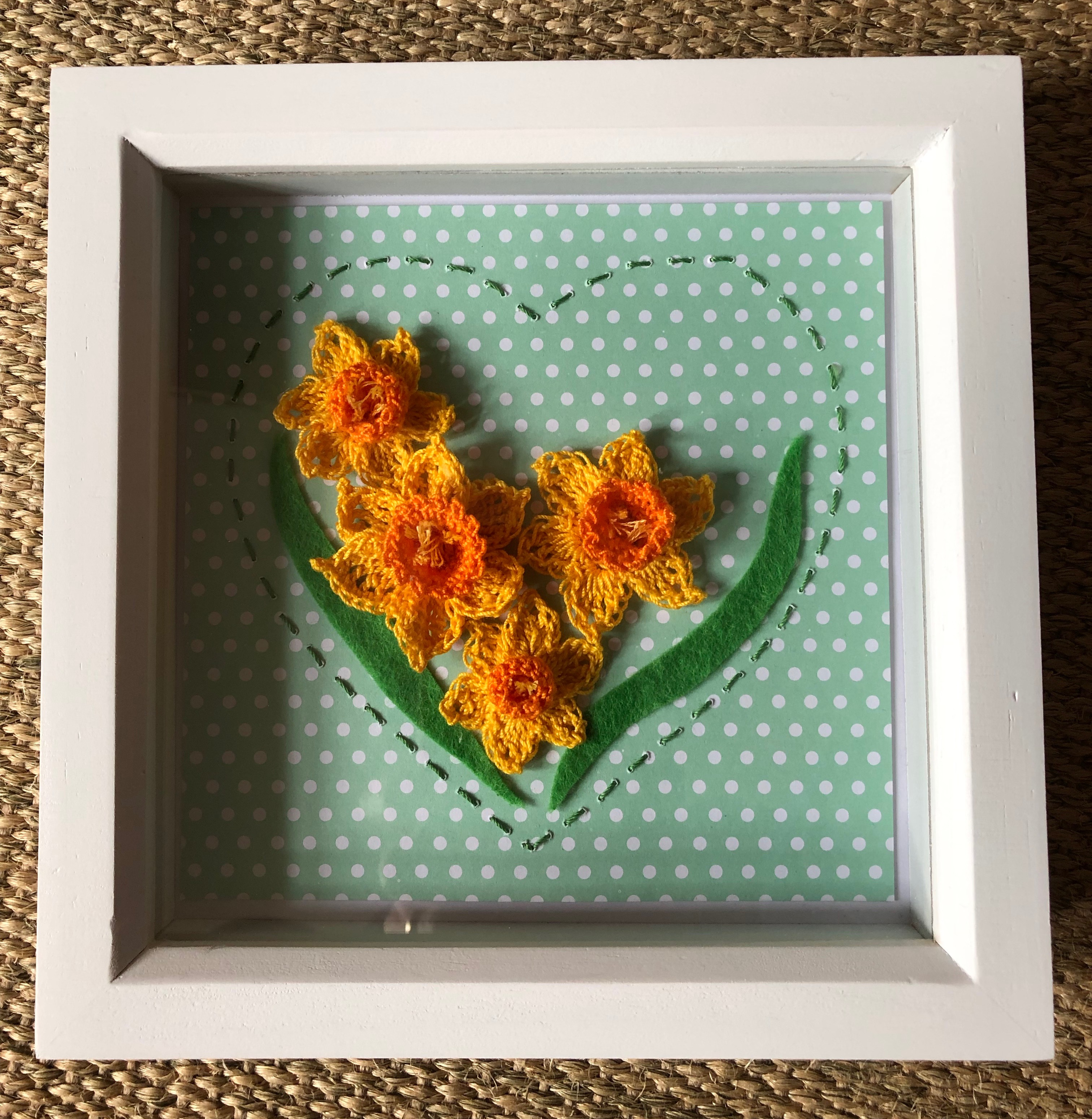 A white wooden framed picture with 4 handmade, crocheted yellow and orange daffodils with green felt leaves surrounded by a hand stitched green heart on a green and white spotty background.