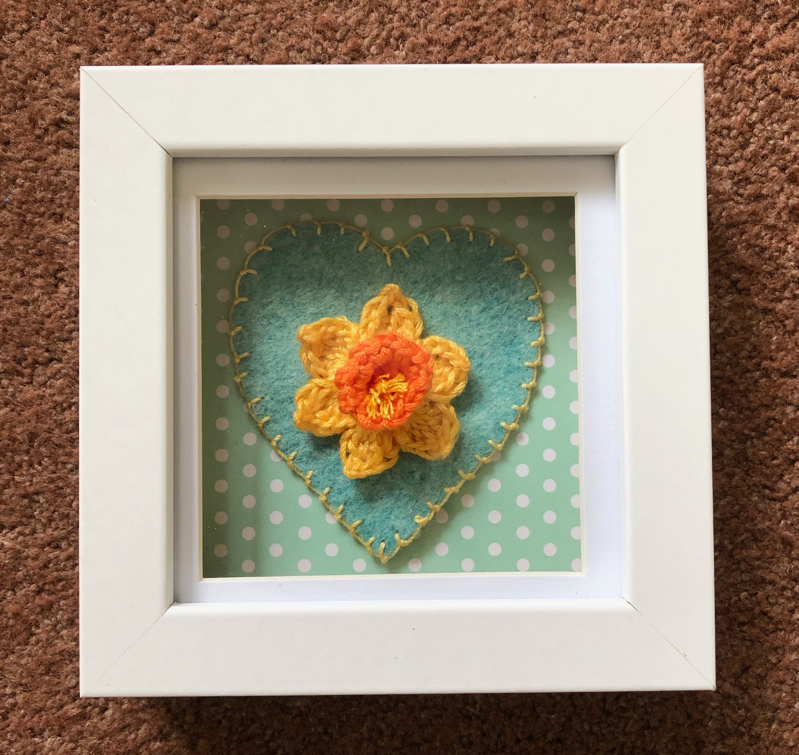 A small white wooden framed picture with a single handmade, crocheted yellow and orange daffodil on top of a hand stitched green and yellow felt heart on a green and white spotty background.