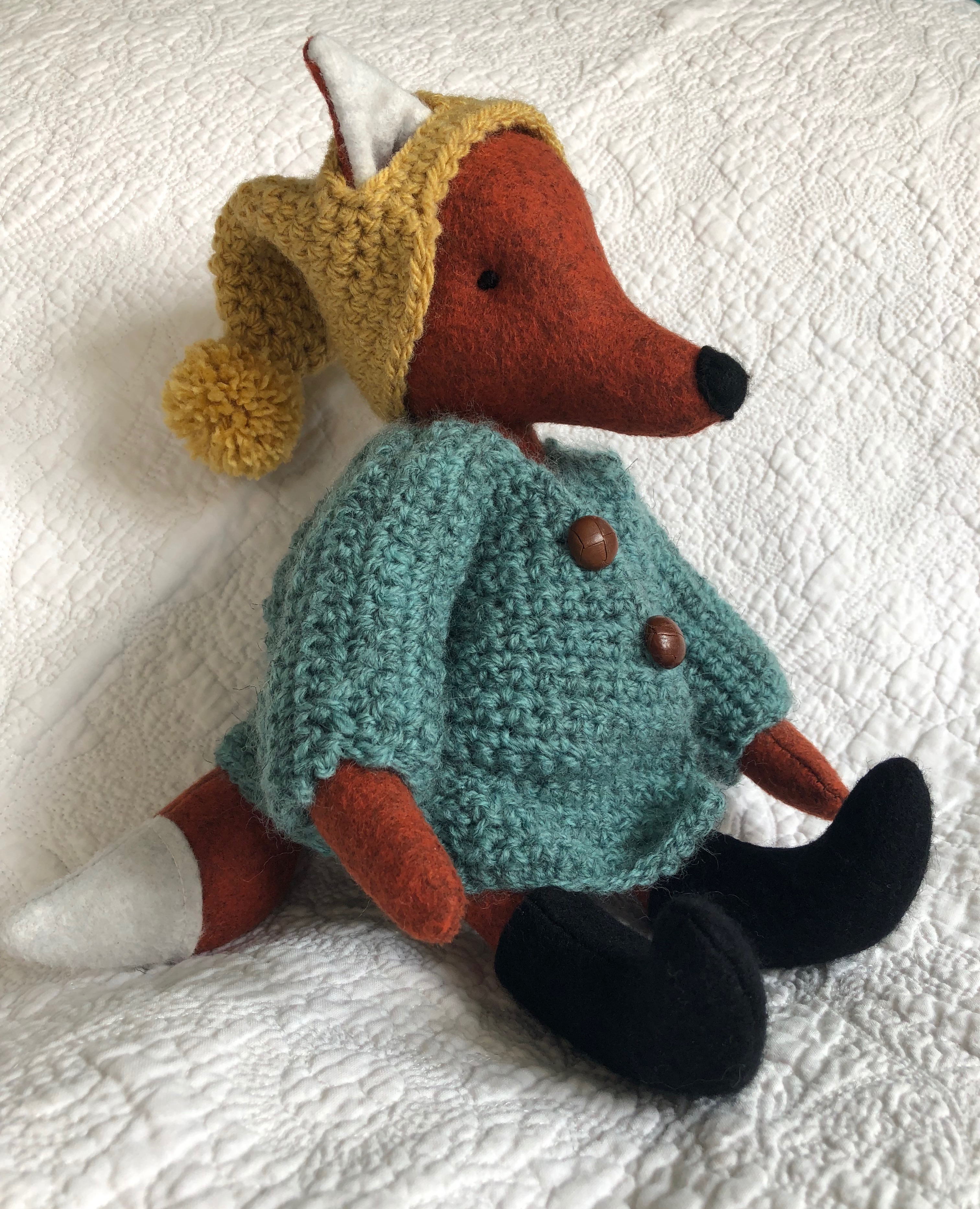 A handmade rusty brown felt fox with a green hand crocheted jacket, mustard yellow bobble hated little black felt boots. Fox pattern by Simone Gooding, crocheted clothes designed and made by me.