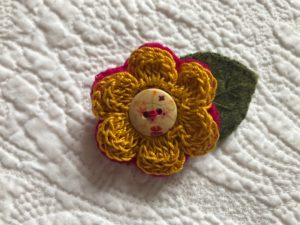 A crocheted mustard coloured cotton flower and green embroidered felt leaf brooch with decorative button detail.