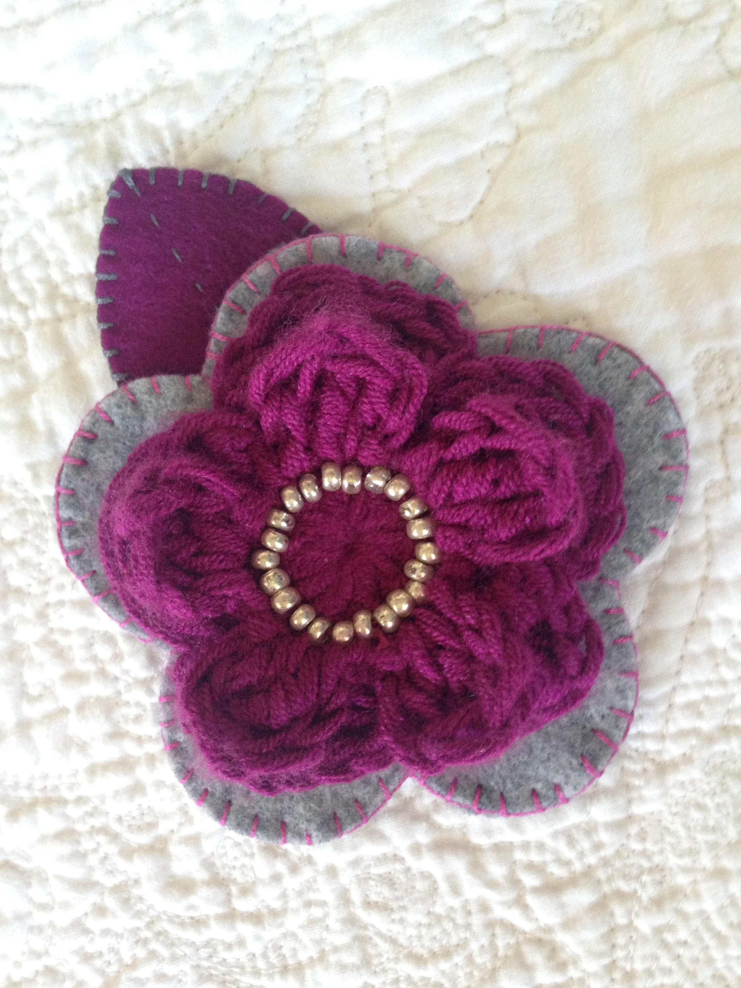 Hand sewn felt and beaded crocheted flower brooch.