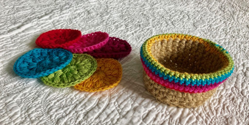 A hand crocheted 100% natural jute basket with 100% cotton crocheted edging detail containing a set of 6 100% cotton crocheted facial pads.