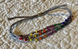 A grey cotton, crocheted and rainbow of colours glass beaded adjustable bracelet.