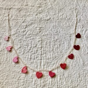 A crocheted garland of tiny hearts in a gradient of pale pink through to burgundy red.