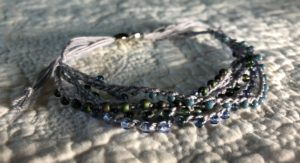 A multi stranded, grey crocheted cotton and glass seed bead bracelet. Using tones of blue and grey glass beads.