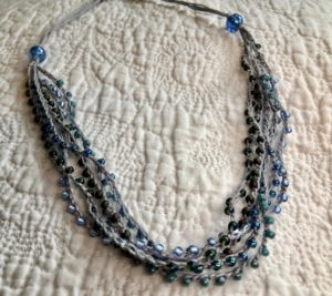 A multi stranded, grey crocheted cotton and glass seed bead necklace. Using tones of blue and grey glass beads.