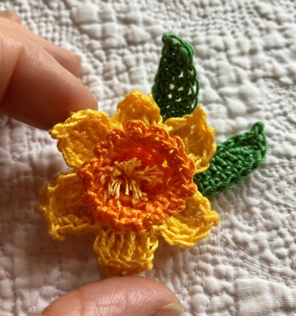 Crocheted daffodil brooch with green leaves.