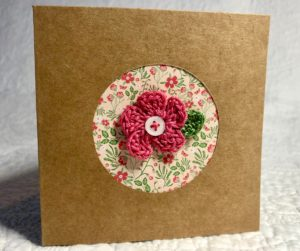A greetings card with a floral circular centre cut out and a crocheted pink flower and green leaf embellishment with button detail.
