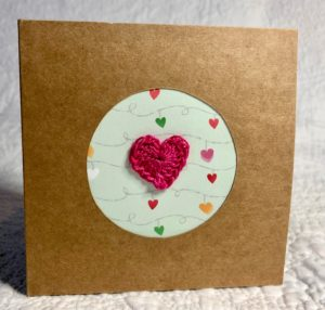 A small square, brown card greetings card with circular cut-out with patterned paper background and crocheted heart embellishment.