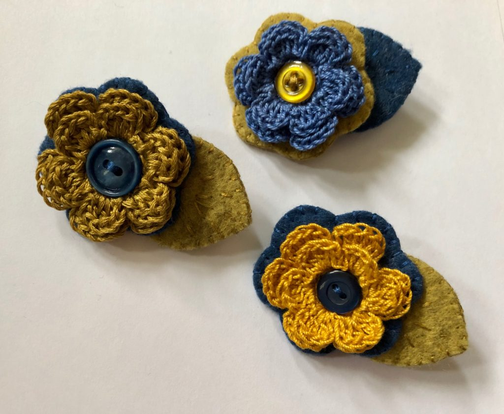 A crocheted cotton flower and embroidered felt leaf brooch with decorative button detail.