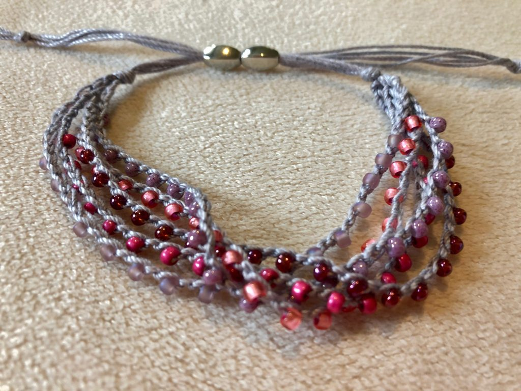 A multi stranded, grey crocheted cotton and glass seed bead bracelet. Using tones of pink glass beads.