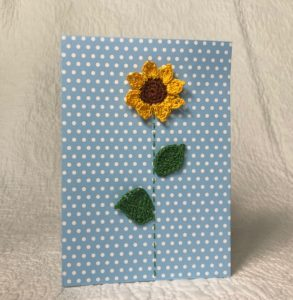 Greetings card. A blue spotty card with a crocheted sunflower and green crocheted leaves.