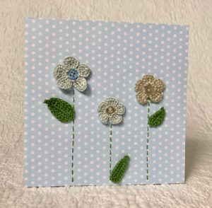 Greetings card. A blue spotty card with three blue and grey crocheted flowers and green crocheted leaves.