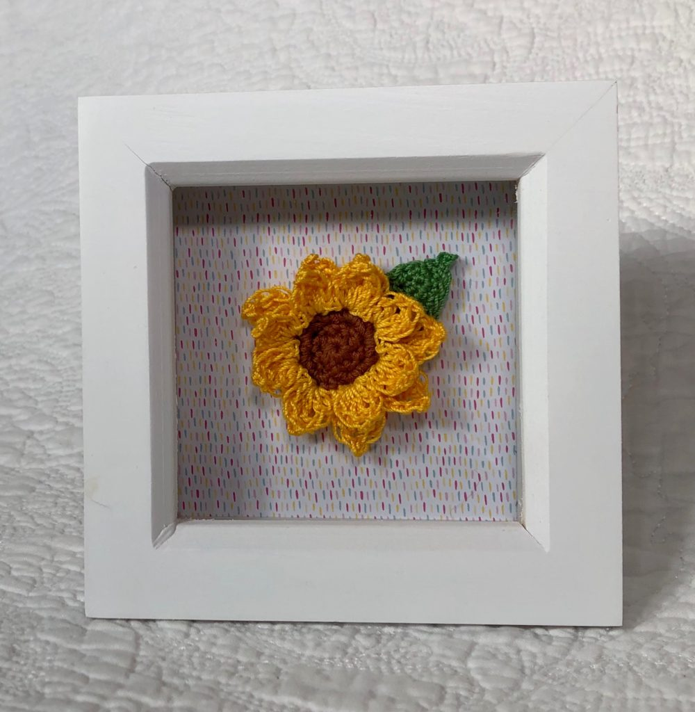 White wooden picture frame with small crocheted sunflower and leaf on a multi coloured paper background.