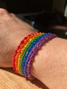 A multi stranded crocheted cotton and beaded adjustable bracelet in a rainbow of colours.