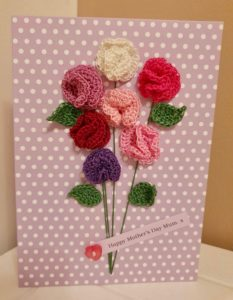 A greetings card with crocheted sweet peas in pinks and green leaves tied in a bunch with a label and button detail on a lilac spotty card.