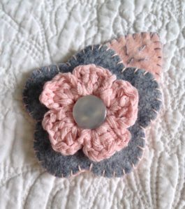 Grey and pale pink hand sewn felt and crocheted flower brooch.