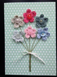 A posy of pastel coloured crocheted flowers with button centres on a spotty greetings card.
