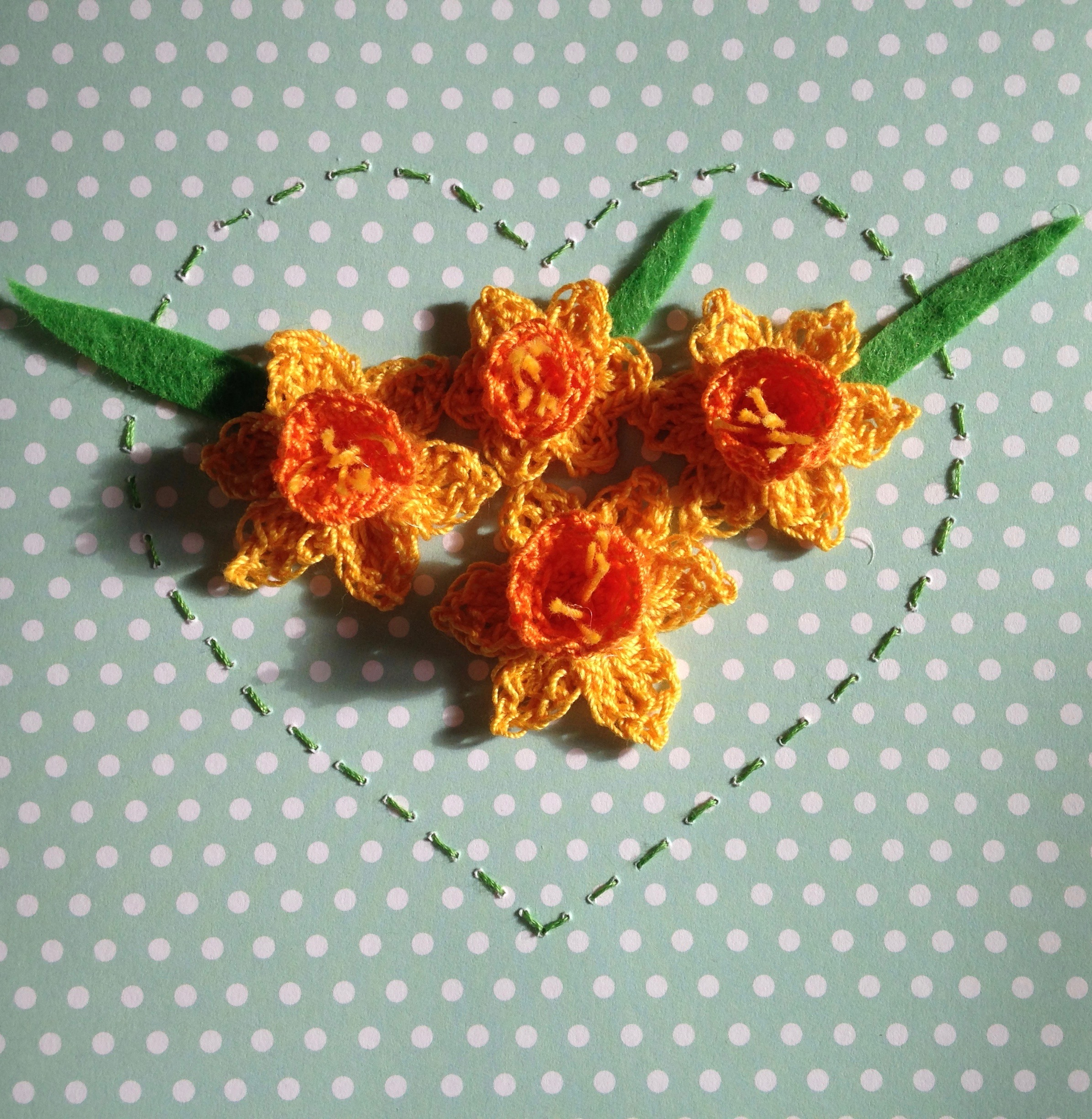 A crocheted Daffodil card. Crocheted Daffodils in yellow and orange surrounded by a hand stitched heart. With a green and white polka dot card background.