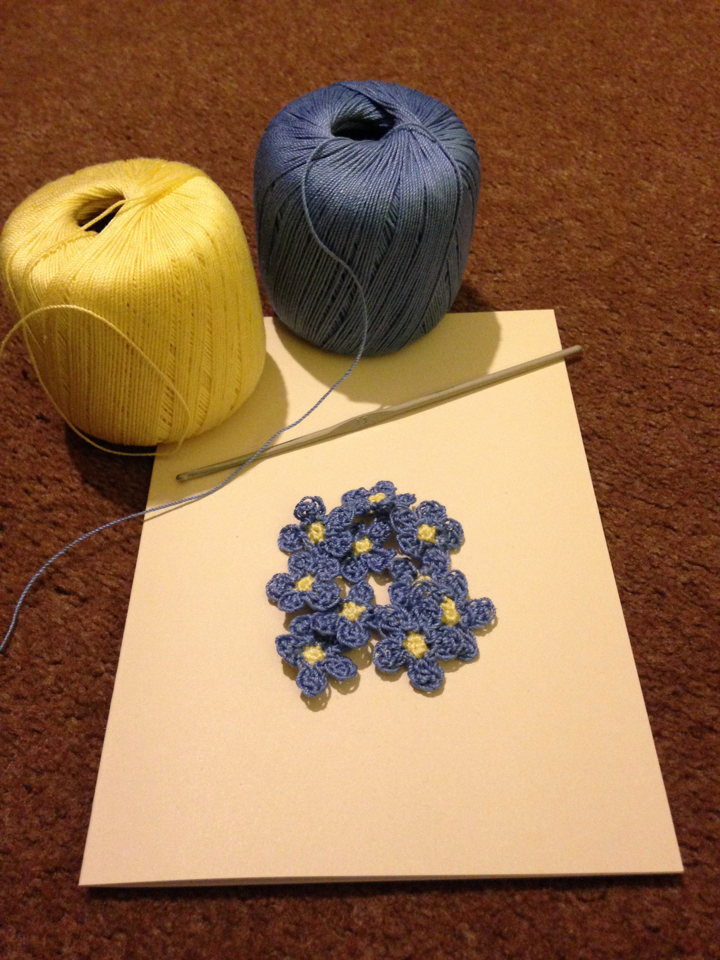 A hand stitched and crocheted greetings card with pale blue Forget-me-not flowers and green leaves.
