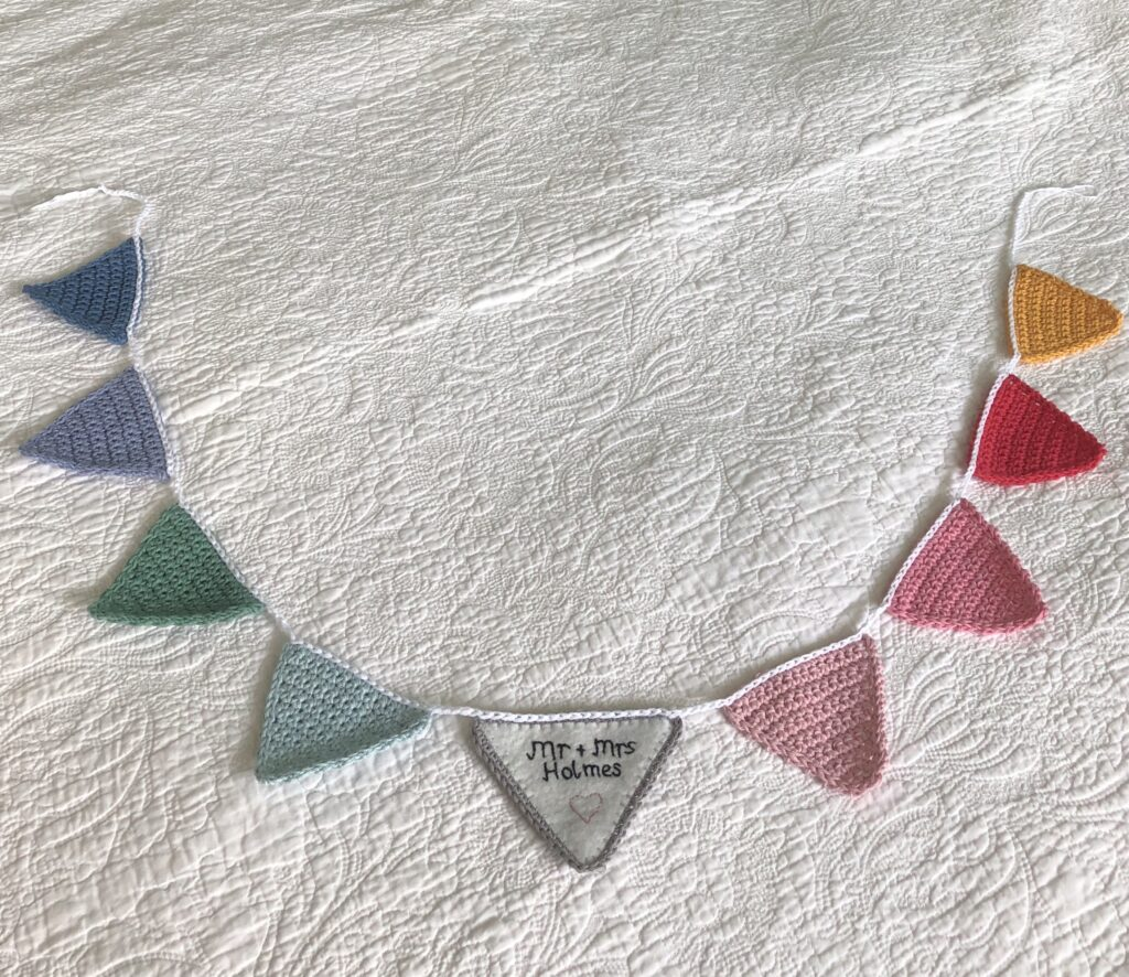 Hand crocheted bunting with personalised and  hand embroidered felt centre flag.