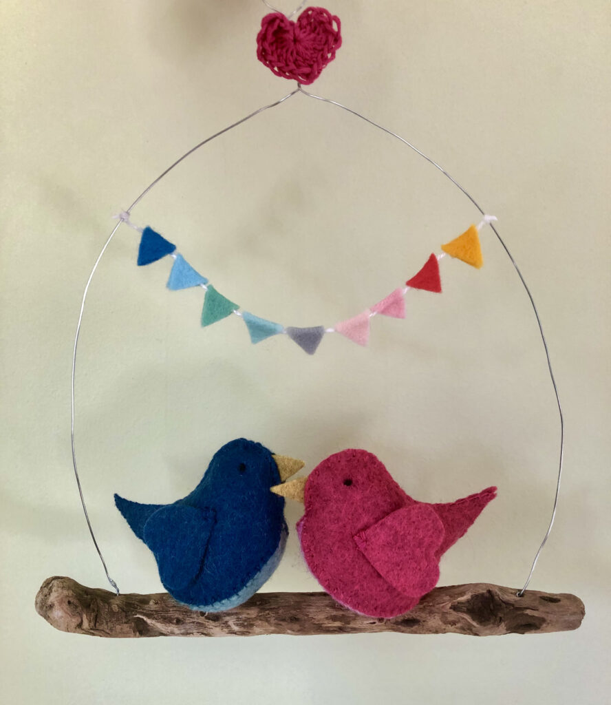 Handmade felt birds and a driftwood hanging perch with felt bunting and crocheted heart.