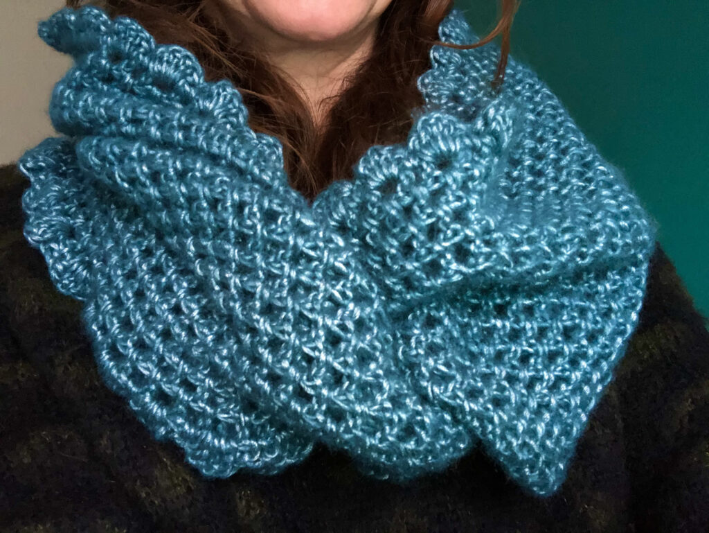 A soft pearl teal coloured hand crocheted infinity scarf.