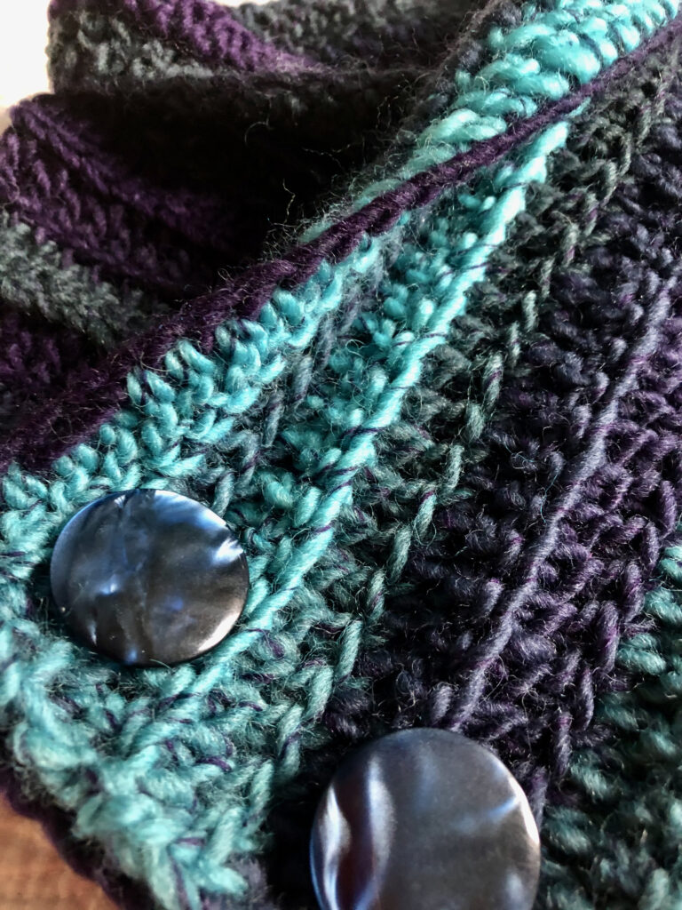 Handmade, crocheted v shaped neck warmer in a variegated colour combination and 3 buttons detail. Made using chunky warm 100% wool.
